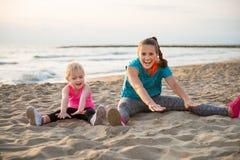 Подходящая молодые мать и дочь сидя на протягивать пляжа Стоковое Изображение