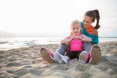 Подходящая молодые мать и дочь сидя на пляже на заходе солнца Стоковые Изображения RF