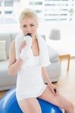 Подходящая питьевая вода женщины пока сидящ на шарике тренировки Стоковая Фотография