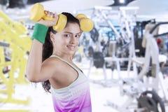 Подходящая разминка женщины с гантелями на спортзале Стоковое Изображение