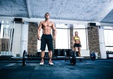 Подходящая разминка человека и женщины на спортзале Стоковая Фотография