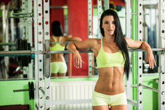 Подходящая склонность женщины на баре веса отдыхая после грубой тренировки в спортзале фитнеса Стоковое Изображение