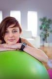 Подходящая склонность женщины на шарике тренировки Стоковые Изображения