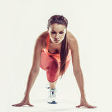 Подходящая спортсменка готовая для того чтобы побежать сверх серая предпосылка Подготавливать женского фитнеса модельный для спри Стоковое фото RF