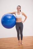 Подходящее брюнет держа шарик тренировки Стоковые Изображения RF