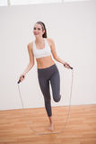 Подходящее брюнет используя прыгая веревочку Стоковое Фото