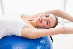 Подходящее брюнет протягивая на шарике тренировки Стоковое Фото