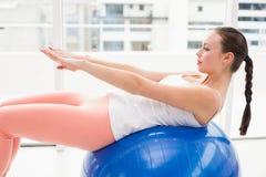 Подходящее брюнет протягивая на шарике тренировки Стоковые Фото