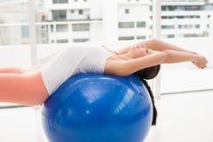 Подходящее брюнет протягивая на шарике тренировки Стоковое фото RF