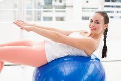 Подходящее брюнет протягивая на шарике тренировки Стоковая Фотография