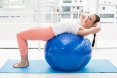 Подходящее брюнет разрабатывая с шариком тренировки Стоковая Фотография
