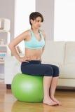 Подходящее брюнет сидя на шарике тренировки Стоковые Фотографии RF