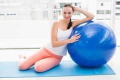 Подходящее брюнет сидя около шарика тренировки Стоковые Фотографии RF