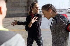 2 подходящее и sporty молодые женщины делая протягивать в городе Стоковая Фотография