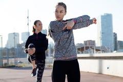 2 подходящее и sporty молодые женщины делая протягивать в городе Стоковое Изображение RF