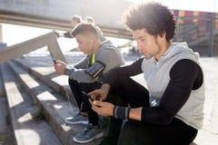 2 подходящее и sporty люди youn используя мобильный телефон в городе Стоковые Изображения