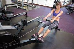 Подходящее усмехаясь брюнет разрабатывая на машине rowing Стоковые Изображения