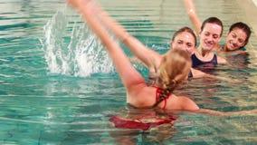 Подходящие женщины делая аэробику aqua в бассейне сток-видео