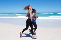 Подходящие молодые женские друзья работая на пляже Стоковые Изображения