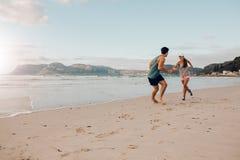 Подходящие молодые пары играя на пляже Стоковое фото RF