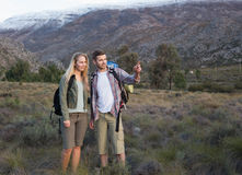 Подходящие молодые пары с рюкзаками на ландшафте Стоковые Фото