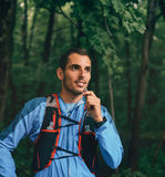 Подходящие мужские гидраты jogger пока тренировка дня для гонки следа леса по пересеченной местностей в природном парке Стоковое фото RF