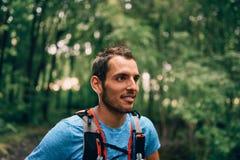 Подходящие мужские остатки jogger во время дня jogging для леса по пересеченной местностей отстают гонку в природном парке Стоковые Фото