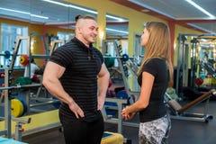 Подходящие привлекательные молодые пары на спортзале смотря таблетк-ПК по мере того как они контролируют их прогресс и фитнес Стоковое фото RF