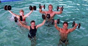 Подходящие люди делая класс аэробики aqua в бассейне с гантелями пены сток-видео