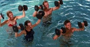 Подходящие люди делая класс аэробики aqua в бассейне с гантелями пены видеоматериал