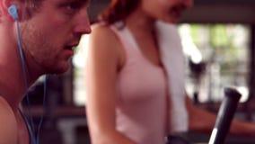 Подходящие люди делая тренировку с эллиптической машиной сток-видео