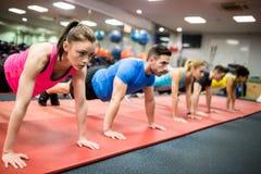 Подходящие люди разрабатывая в классе фитнеса Стоковая Фотография