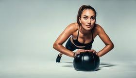 Подходящий делать женщины нажимает вверх на шарике медицины Стоковые Фотографии RF