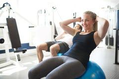 Подходящий делать молодой женщины Сидеть-поднимает на шарике тренировки Стоковая Фотография RF