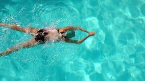 Подходящий женский пловец делая ход груди в бассейне акции видеоматериалы