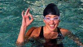 Подходящий женский пловец показывая о'кеы подписывает внутри бассейн акции видеоматериалы