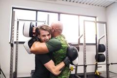 Подходящий испанский человек в боксе спортзала при его тренер, обнимая Стоковые Изображения