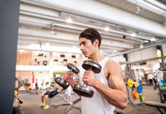 Подходящий испанский человек в спортзале разрабатывая с весами Стоковые Фото
