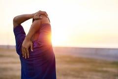 Подходящий молодой человек протягивая его плеча перед бегом утра Стоковое Изображение