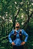 Подходящий мужской jogger отдыхая во время тренировки дня для гонки следа леса по пересеченной местностей в природном парке Стоковые Изображения RF