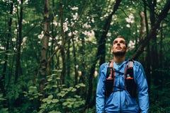 Подходящий мужской jogger отдыхая во время тренировки дня для гонки следа леса по пересеченной местностей в природном парке Стоковая Фотография RF