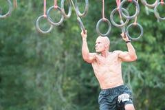 Подходящий мужчина схватывает кольца в весьма гонке полосы препятствий Стоковые Фото
