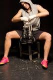 Подходящий мышечный молодой боксер кладя на его перчатки стоковое фото