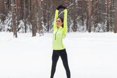 Подходящий протягивать женщины, нагревая зиму утра Стоковая Фотография RF
