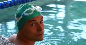 Подходящий пловец усмехаясь вверх на камере в бассейне сток-видео