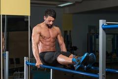 Подходящий спортсмен делая тренировку на параллельных брусьях Стоковые Фотографии RF