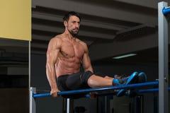 Подходящий спортсмен делая тренировку на параллельных брусьях Стоковые Изображения