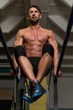 Подходящий спортсмен делая тренировку на параллельных брусьях Стоковое Фото