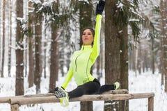 Подходящий спортсмен женщины делая левой протягивать разделенный ногой работает outdoors в древесинах Работать женских спорт моде Стоковое фото RF