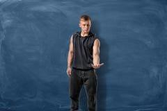 Подходящий человек в черном положении на голубой предпосылке доски и смотреть его руку Стоковые Изображения RF